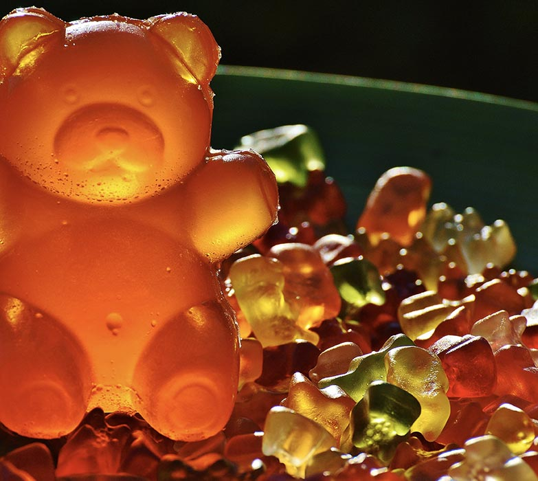 This pictures shows a giant gummy bear among smaller gummy bears, to illustrate the amount of sugar we eat each day.