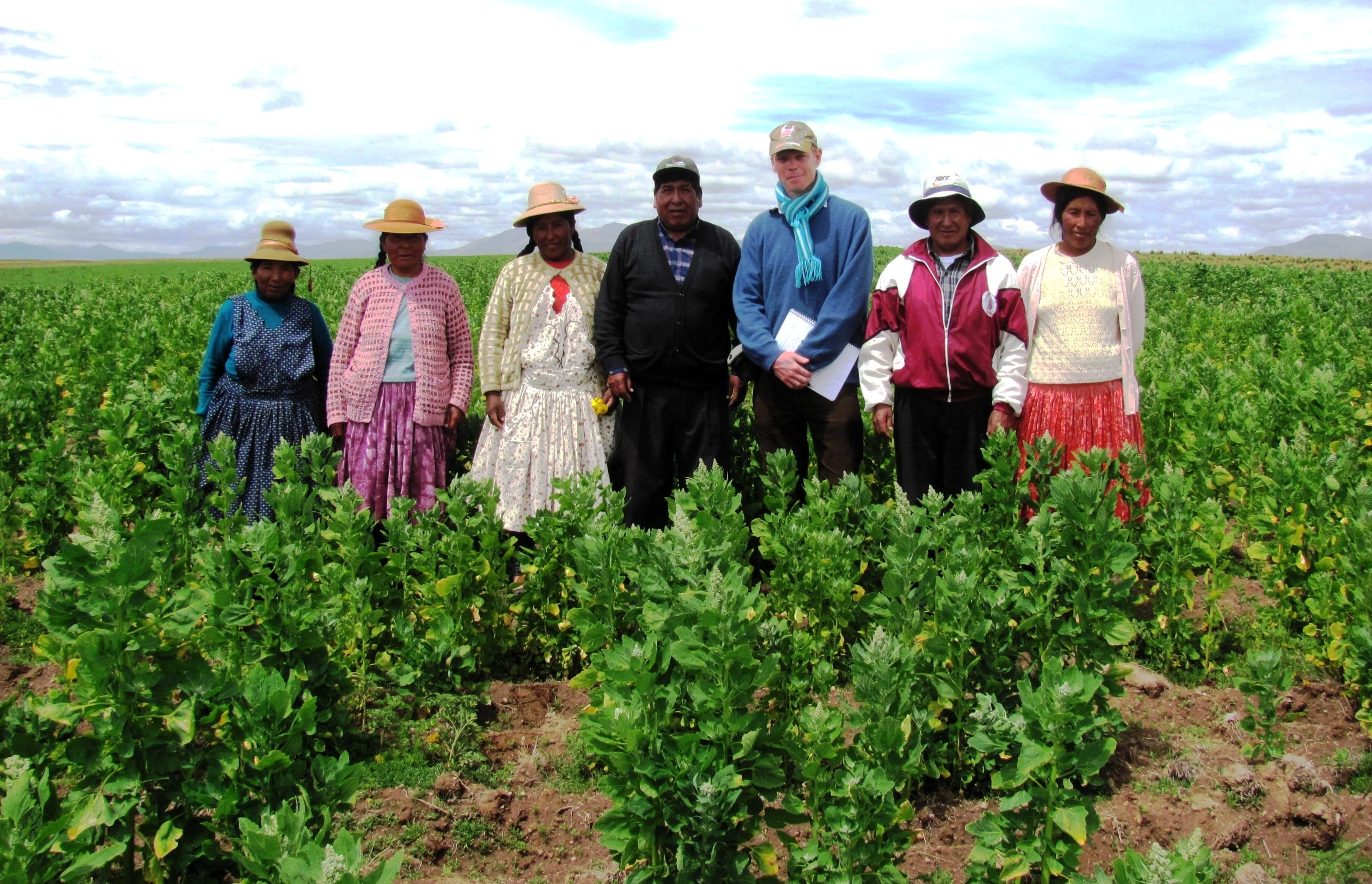 James and the farmers in a quinoa field. The farmers are wearing traditional Peruvian clothing and hats. James stands in the middle.
