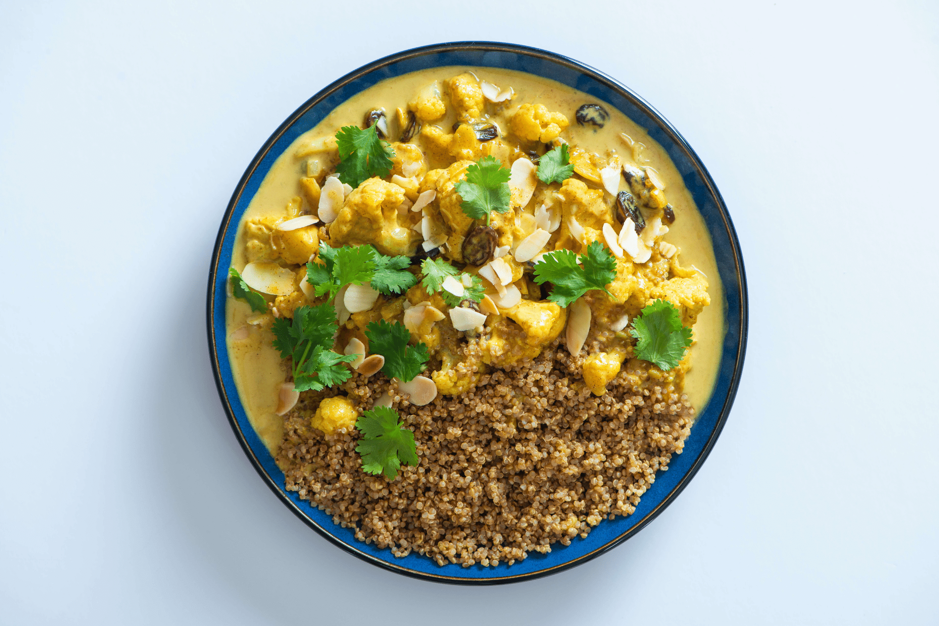 A blue bowl with yellow cauliflower curry topped with coriander and wholegrain quinoa
